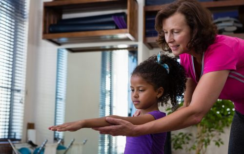Female physiotherapist helping girl patient in performing exercise with dumbbell  in clinic